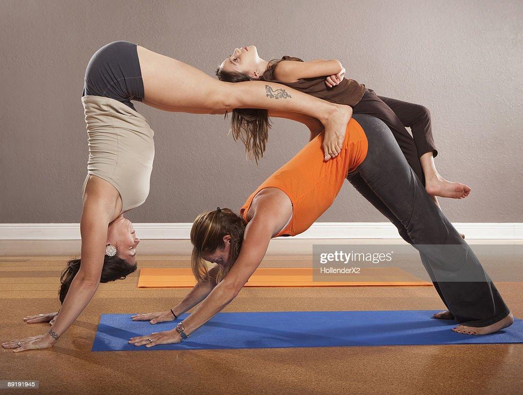 women doing yoga poses with girl on back stock photo