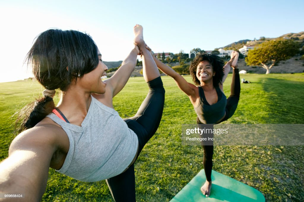 women doing yoga together in green field : Stock-Foto