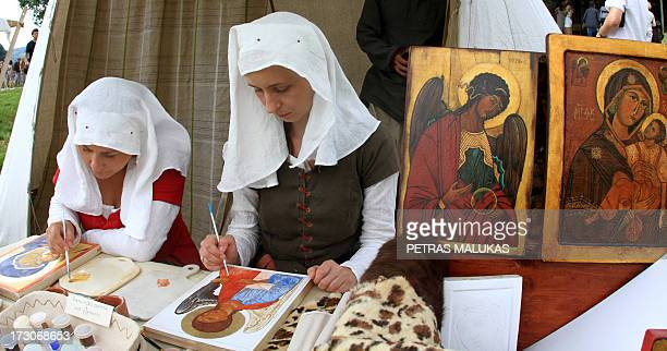 Women draw religious icons during the experimental archeology festival 'Days of Live Archaeology in Kernave' in the old capital Kernave Lithuania on...