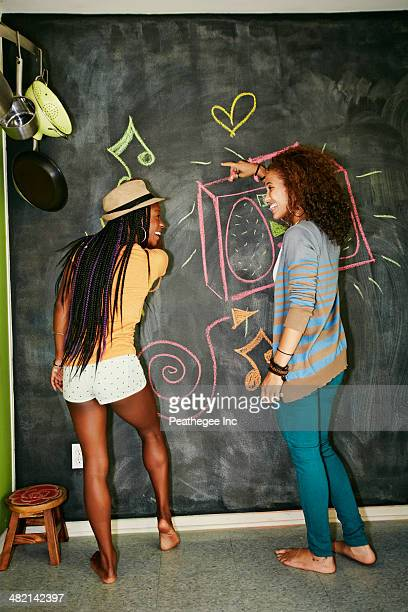 Women drawing on blackboard wall