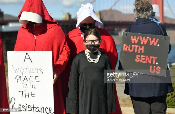 Women dressed as characters from The Handmaid's Tale and late Supreme Court Justice Ruth Bader Ginsberg hold signs during a celebration march for...