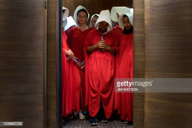 TOPSHOT Women dressed as characters from the novelturnedTV series The Handmaid's Tale stand in an elevator at the Hart Senate Office Building as...