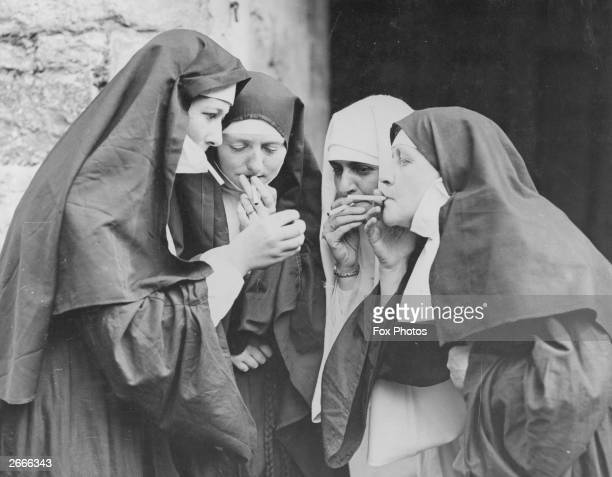 Women dressed as nuns have a cigarette break during the Walmer Castle pageant in Kent