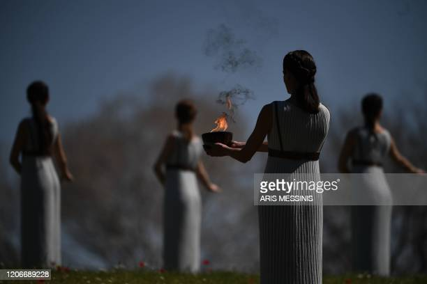 Women dressed as priestesses take part in the Olympic flame lighting ceremony in ancient Olympia, ahead of Tokyo 2020 Olympic Games on March 12, 2020.