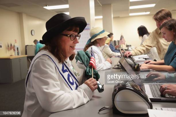 Women dressed as suffragettes check in to receive a ballot for the midterm elections at the Polk County Election Office on October 8 2018 in Des...