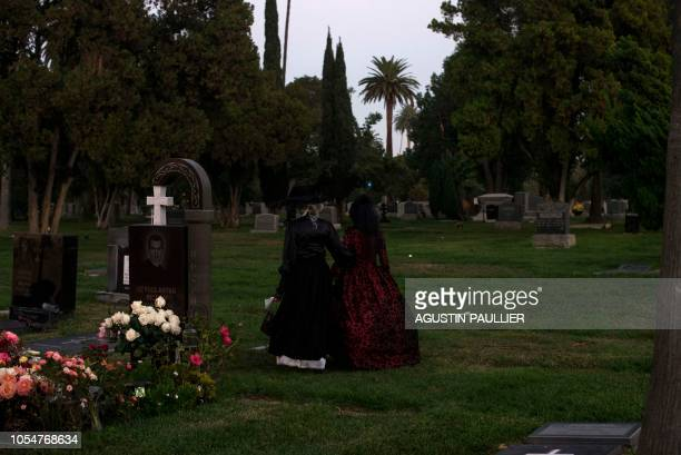 Women dressed as the Catrina the Mexican traditional representation of death walk among headstones during Hollywood Forever Cemetery's 19th annual...