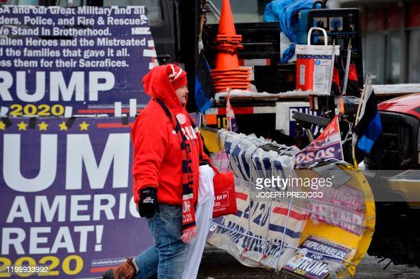 Women dressed in a Trump sweater walks by signage outside outside the SNHU arena hours ahead of US President Donald Trump's rally in Manchester, New...
