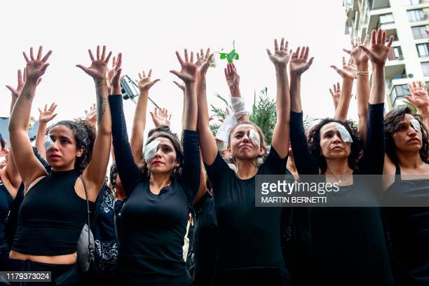 TOPSHOT Women dressed in black and wearing eye patches representing protesters injured with pellets shot by riot police raises ther hands as they...