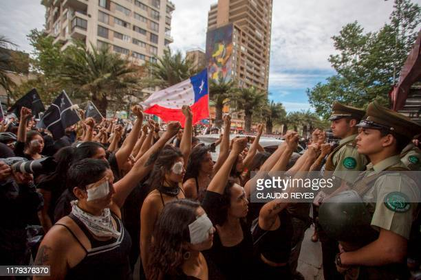 Women dressed in black and wearing eye patches representing protesters injured with pellets shot by riot police raise their wrists to a line of...