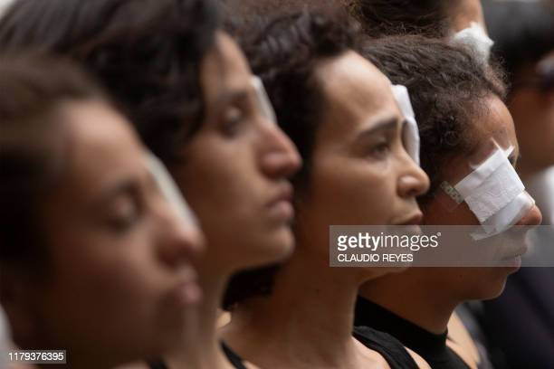 Women dressed in black and wearing eye patches representing protesters injured with pellets shot by riot police take part in the socalled 'Mourning...