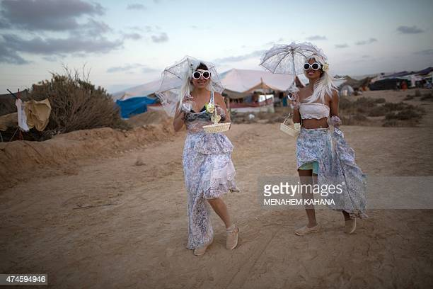 Women dressed in costumes walk with their umbrellas during the 2015 Midburn festival in the Negev Desert near the Israeli kibbutz of Sde Boker on May...