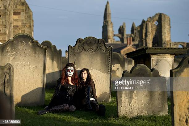 Women dressed in gothic costumes pose for pictures during the biannual 'Whitby Goth Weekend' festival in Whitby Northern England on November 2 2014...