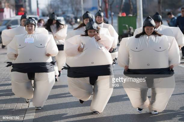 Women dressed in inflatable sumowrestler costumes run in a competition on the International Women's Day on March 8 2018 in Taiyuan Shanxi Province of...