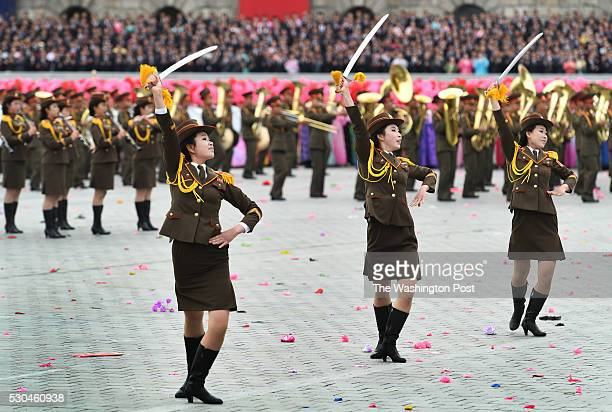Women dressed in military outfits dance with swords in a parade at Kim Il Sung Square in Pyongyang North Korea on May 1 2016 The parade and...