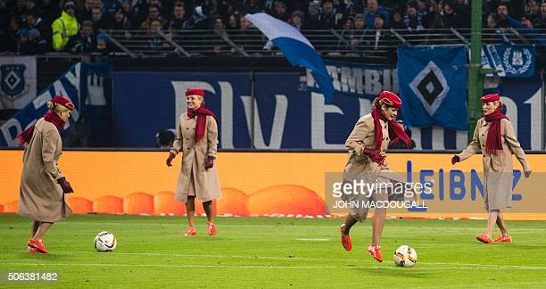 Women dressed in stewardess uniforms of UAE airline Emirates kick a football around the pitch before the start of the German first division football...