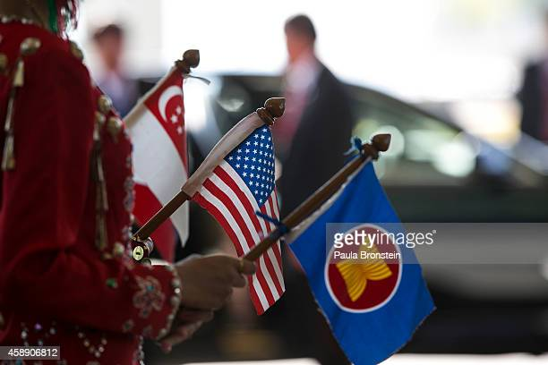 Women dressed in traditional costume hold flags standing at the arrival hall on the second day of the ASEAN summit on November 13 2014 in Naypyidaw...