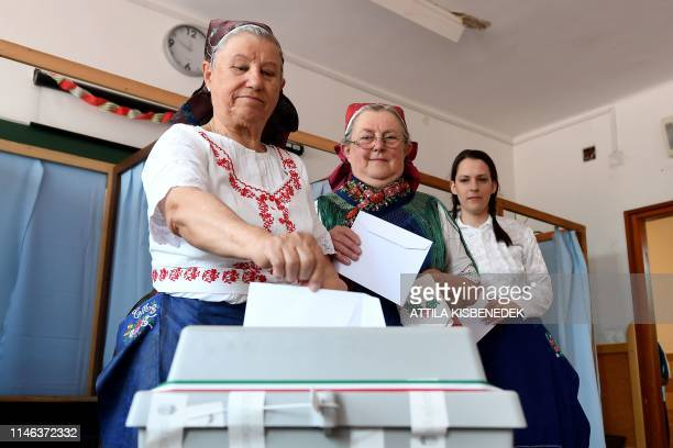 Women dressed in traditional Hungarian outfits vote for the European elections at a polling station in a school in Veresegyhaz near Budapest on May...