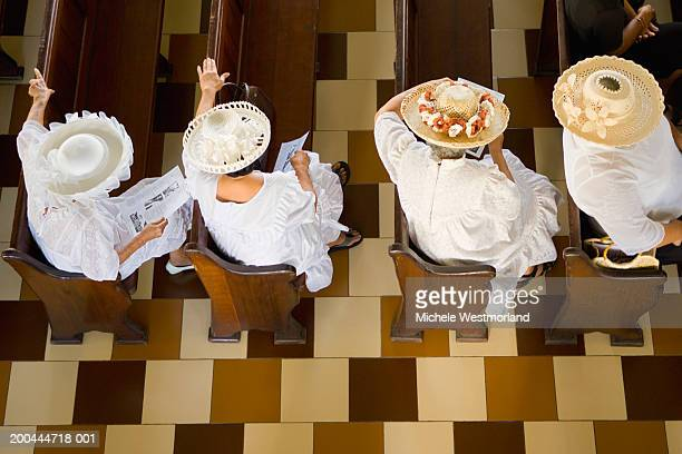women dressed in white, wearing hats, sitting in church, elevated view - 一張羅 ストックフォトと画像