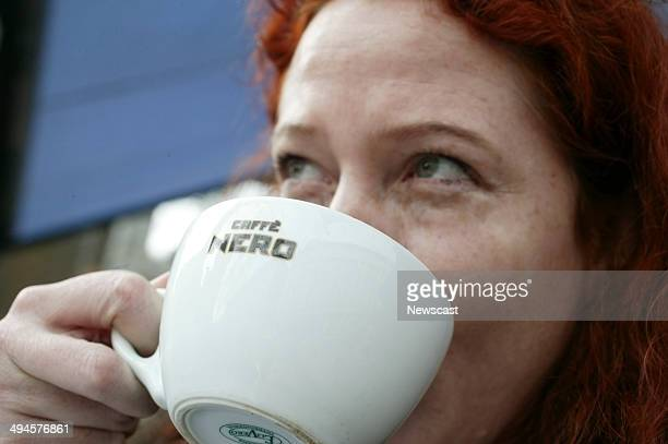 A women drinking a cup of coffee outside a Caffe Nero cafe