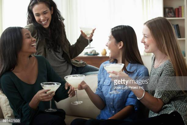 Women drinking cocktails in living room