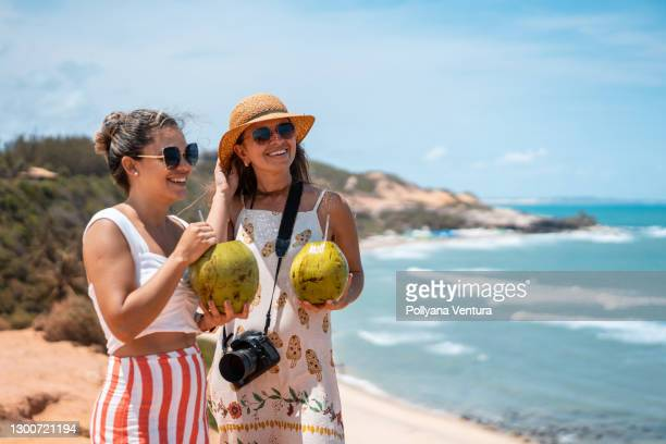 women drinking coconut water at praia do amor in rio grande do norte - natal brazil stock pictures, royalty-free photos & images