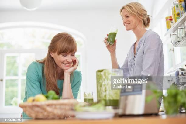 women drinking green vegan smoothie in kitchen - körperbewusstsein stock-fotos und bilder