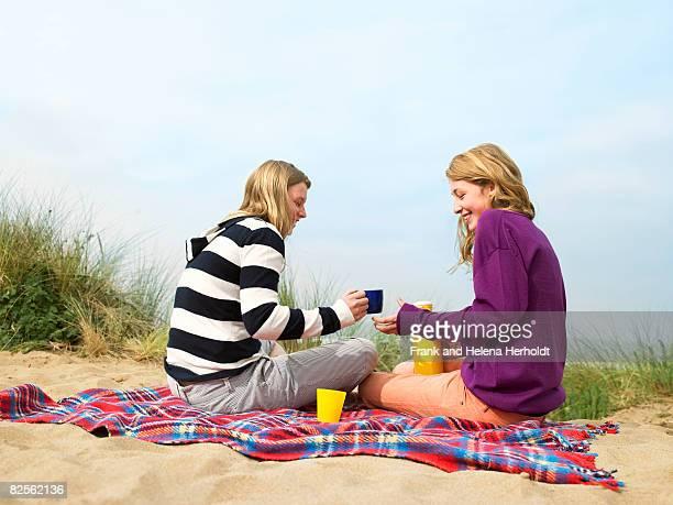 Women drinking hot drink, on blanket