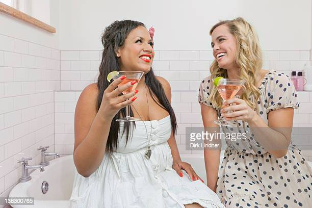 women drinking martinis in bathroom - evening gown stock pictures, royalty-free photos & images