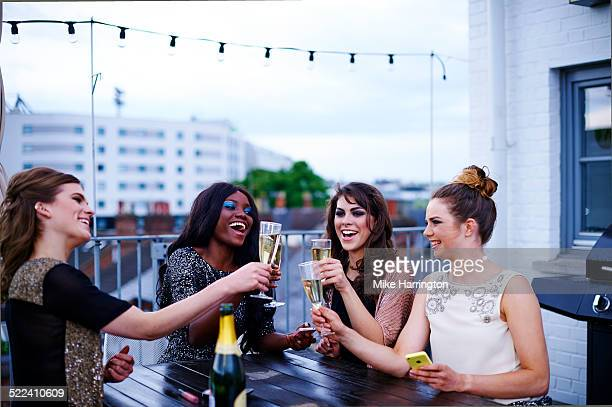 Women drinking outside on urban rooftop garden.