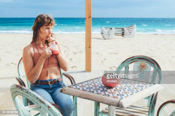 Women drinking smoothie on the beach