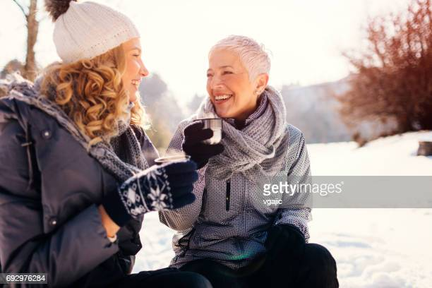 women drinking tea outdoors at winter - winter sport stock pictures, royalty-free photos & images