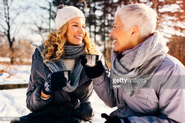 Women Drinking Tea Outdoors At Winter