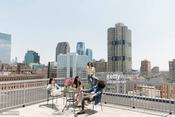 Women drinking wine on urban rooftop