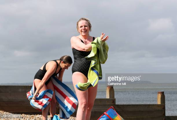 women dry themselves after open water swimming - showus stock pictures, royalty-free photos & images