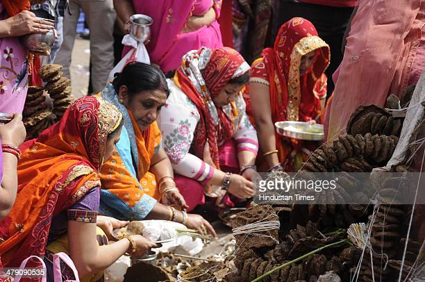 Women during the Holi puja at Sadar Bazar on March 16 2014 in Gurgaon India The festival falls on the last full moon day of Falgun according to Hindu...