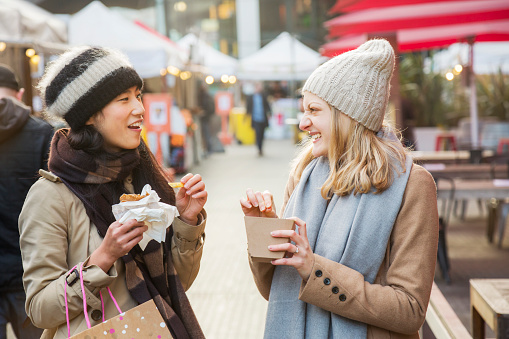 Women eating and chatting, while walking through outdoor food market. - gettyimageskorea