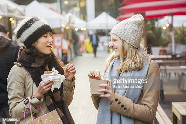 women eating and chatting, while walking through outdoor food market. - street food stock pictures, royalty-free photos & images