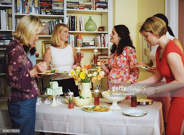 Women eating at baby shower buffet