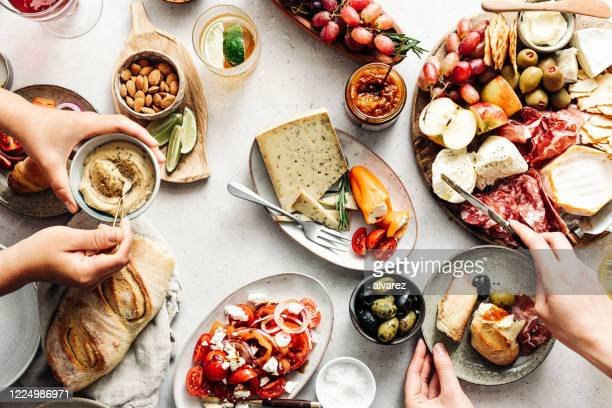women eating fresh mediterranean platter on table - antipasto stock pictures, royalty-free photos & images