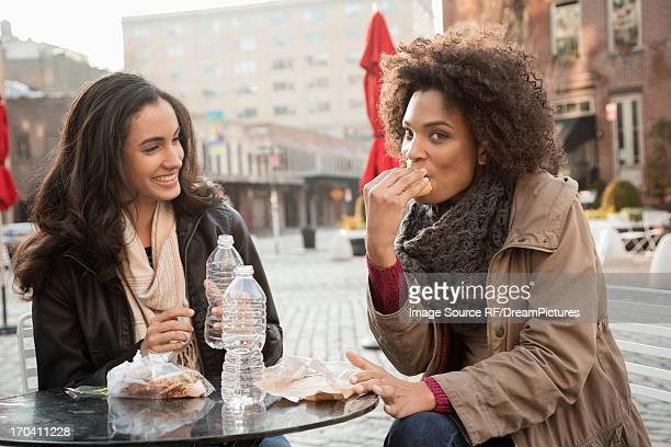 Women eating together at sidewalk cafe