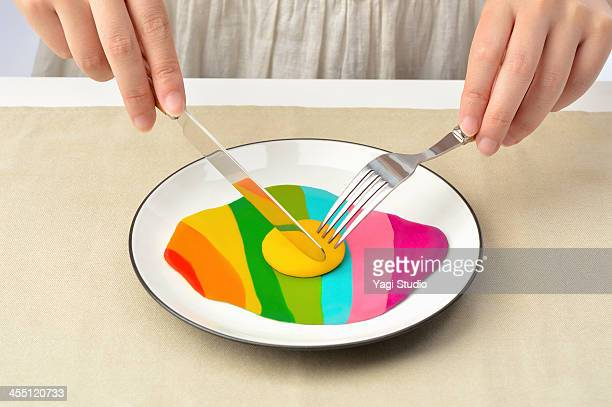 Women eating with a fork and knife colorful egg