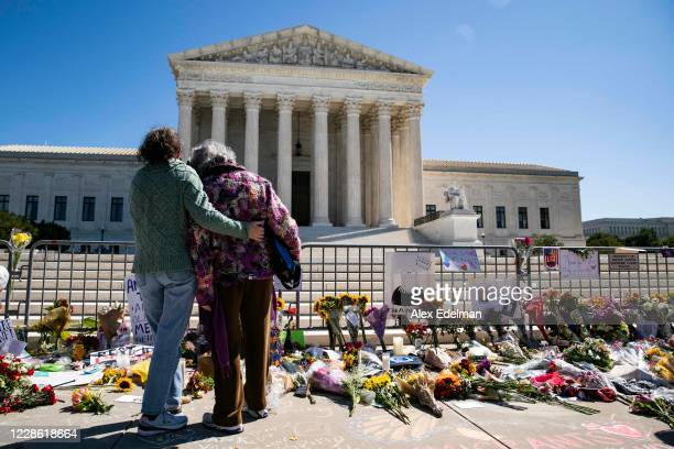 Women embrace at a makeshift memorial for late Supreme Court Justice Ruth Bader Ginsburg on the steps of the United States Supreme Court on September...