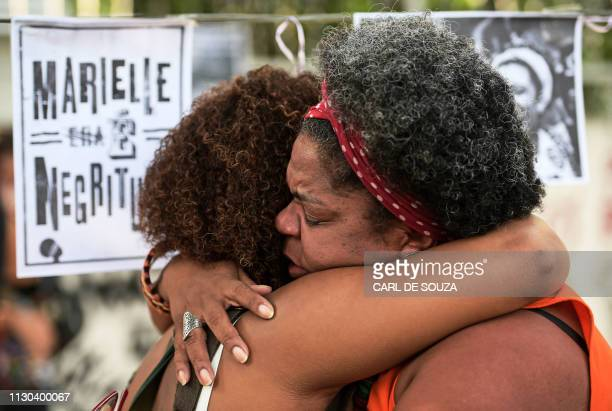 Women embrace during a protest marking one year of the death of Brazilian councilwoman Marielle Franco at the site where she was murdered in Rio de...