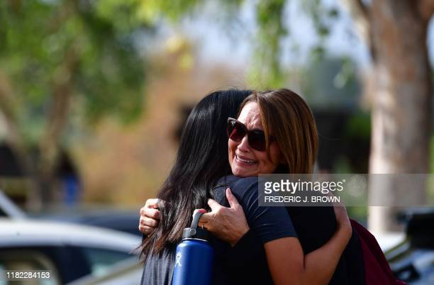 TOPSHOT Women embrace in Central Park after a shooting at Saugus High School in Santa Clarita California on November 14 2019 At least four people...