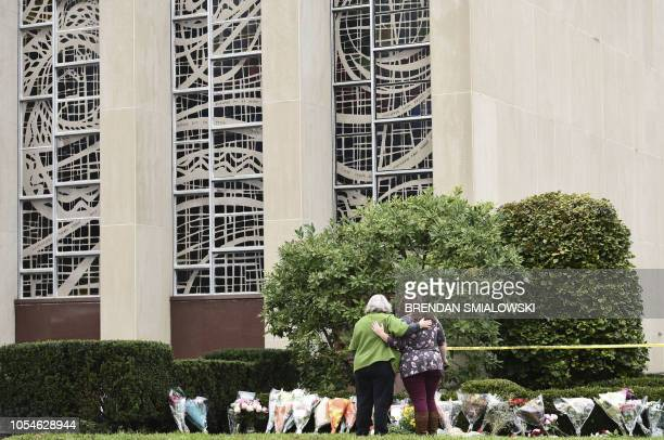 Women embrace in front of memorial flowers on October 28 2018 outside of the Tree of Life Synagogue after a shooting there left 11 people dead in the...