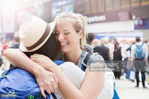 Women embracing, greeting at train station