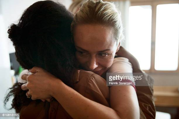 2 women embracing - female friendship stock pictures, royalty-free photos & images