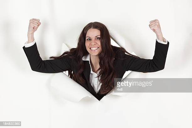 women emerging through a hole in paper and clenching fists - appearance stock photos and pictures