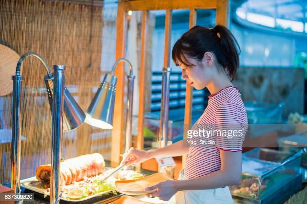 グアムのリゾート ホテルでビュッフェ スタイルの食事を取る女性ジョセイ