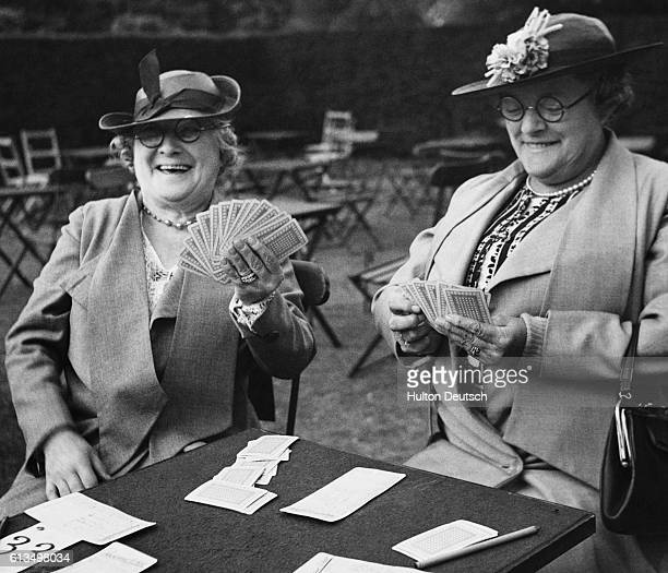 Women enjoy a friendly game of cards at an outdoor bridge competition for prizes